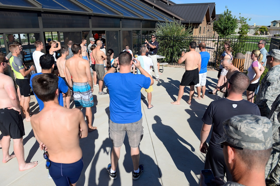 Competitors listen as Seth Cannello, Schriever Air Force Base Fitness Center director, explains rules of the 11th annual Schriever Air Force Base Triathlon, Friday, Aug. 14, 2015, outside the Tierra Vista community center pool at Schriever Air Force Base, Colorado.  The competitors first swam 800 meters in the pool and rode 12 miles on a bicycle before finishing the event with a 3.1-mile run. (U.S. Air Force photo/Christopher DeWitt)