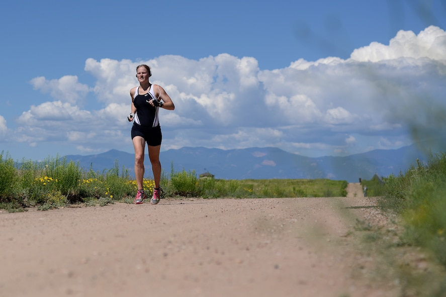 Jennifer Titkemeier, Air Force Space Command, completes the final stage of the 11th annual Schriever Air Force Base Triathlon, Friday, Aug. 14, 2015, on the running trail at Schriever Air Force Base, Colorado.  Titkemeier took first place in the female division, completing the 800-meter swim, 12-mile bike, and 3.1-mile run in 1:27:30. (U.S. Air Force photo/Christopher DeWitt)
