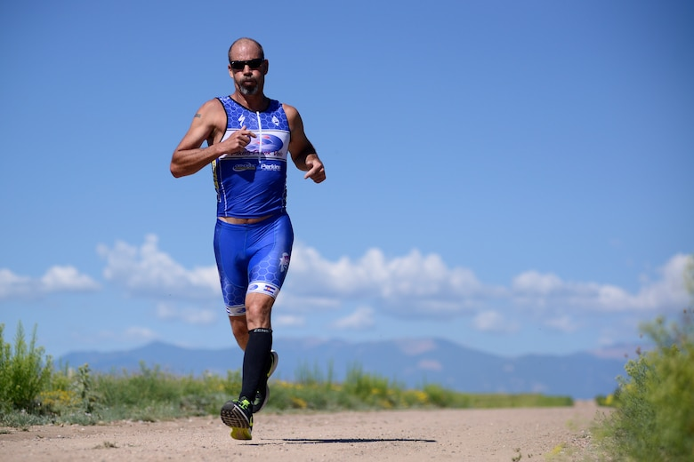Woody Noleen, retired, completes the final stage of the 11th annual Schriever Air Force Base Triathlon, Friday, Aug. 14, 2015, on the running trail at Schriever Air Force Base, Colorado.  Noleen won the male division completing the 800-meter swim, 12-mile bike, and 3.1-mile run in 1:09:26. (U.S. Air Force photo/Christopher DeWitt)