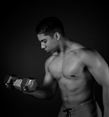 Senior Airman Miguel Amador, 5th Medical Group medical information service technician, lifts a dumbbell at Minot Air Force Base, N.D., Aug. 11, 2015. Amador competes in bodybuilding competitions and has finished as well as second place. (U.S. Air Force photo/Airman 1st Class Christian Sullivan)