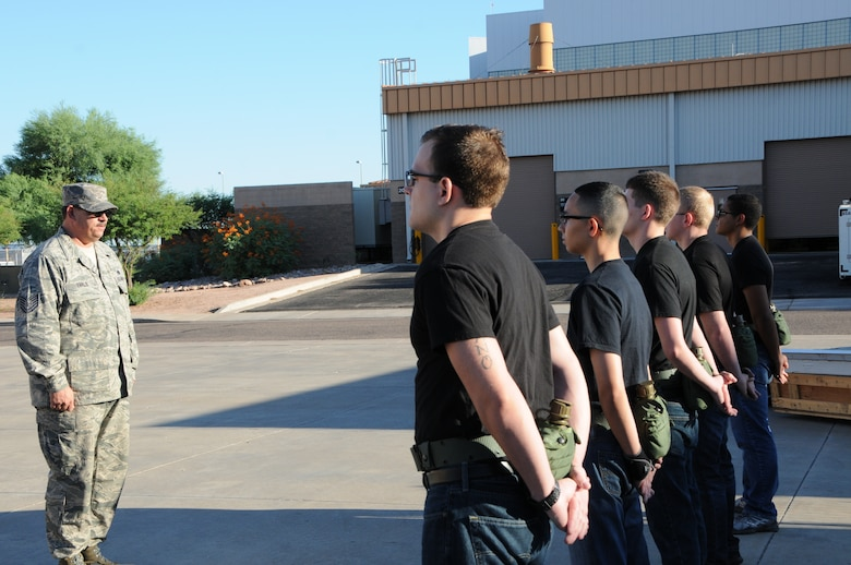 Tech. Sgt. Bret Earls, 161st Air Refueling Wing student flight instructor and former U.S. Army drill instructor, inspects a formation of trainees at the Phoenix Air National Guard Base, Aug. 2. The main purpose of the student flight is to in-process new recruits into the wing and then out-process them to basic training and technical school; however, a secondary benefit is the mentorship the trainees receive from the student flight's instructors. (U.S. Air National Guard photo by Tech. Sgt. Michael Matkin)