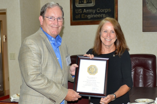 The Honorable Jo-Ellen Darcy, assistant secretary of the Army for Civil Works, presents Mike Wilson, U.S. Army Corps of Engineers Nashville District deputy for Programs and Project Management, with a certificate recognizing his 40 years of service during a stakeholder meeting with the Mississippi River Commission onboard the Motor Vessel Mississippi while docked in Clarksville, Tenn., Aug. 11, 2015.