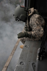 California Army National Guard Staff Sgt. Alexander Martinez, crew chief from the 1106 Theater Aviation Sustainment Maintenance Group, operates on a UH-60 Black Hawk over the Fork Complex in Shasta and Trinity Counties, California, Aug. 17, 2015.