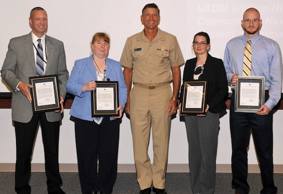 "DAHLGREN, Va. - NSWC Dahlgren Division awardees Christopher Nerney, Donna Wheater, Melanie Lunney and David Luck, l to r, are pictured with Vice Adm. William Hilarides, commander, Naval Sea Systems Command, moments after the admiral presented them with letters of appreciation at an Aug. 11 awards ceremony. Hilarides commended the team, including Michael Clark and Adrienne Phaler, for supporting the Cybersecurity Technical Exchange Meeting sponsored by NAVSEA. ""This meeting brought together leaders from Naval Sea Systems Command, Naval Air Systems Command, Space and Naval Warfare Systems Command, and United States Tenth Fleet in one place to discuss and 'connect the dots' pertaining to cyber-related work spanning the Navy enterprise,"" said Hilarides in the letter. ""Your behind the scenes involvement in this technical exchange was paramount, enabling both current and future cyber deliberations that are of the highest importance to the Navy."" Describing the accomplishment as ""a major milestone in charting Naval Sea Systems Command's way ahead for the Navy's implementation of the cybersecurity mission priority,"" Hilarides thanked, ""the men and women of NSWCDD for taking a stake in the Navy's ability to promote cybersecurity operations through technical excellence and accountability."""