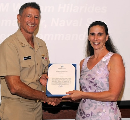 "DAHLGREN, Va. - Vice Adm. William Hilarides, commander, Naval Sea Systems Command, presents the Navy Meritorious Civilian Service Award to Marie Colitti at an Aug. 11 awards ceremony. Hilarides congratulated Colitti and nine of her colleagues  - James Morrissett, Troy Bentz, Lorilee Geisweidt, Amanda Cardiel, Steven Sovine, Keith Manion, Meredith Murray, Jeffery McConnell and Christopher Knowlton - who also received the award for their impact on the Small Surface Combatant Task Force last year. ""In response to the Secretary of Defense-directed study of a more lethal and more survivable small surface combatant, these recipients used their professional expertise to assist in the development of an extraordinary body of work that establishes the direction for a significant portion of the U.S. Navy shipbuilding and Force capability that reaches deep into this century,"" according to the citation. ""The unassailable logic, method, and results that these recipients exhibited and applied to this task, provided the Department of the Navy and Department of Defense with the confidence it needs to make decisions of such high importance."""