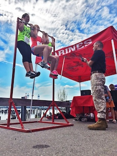 (Left to right) Rachel Erin, Heidi Lewellyn and Faith Swenson conduct flex-arm hangs for time at the Marine tent during the Urban Raid Portland 5K obstacle run, Aug. 15. The three Marines at the event ran the race and placed second in the team category and one poolee placed third in his age group.