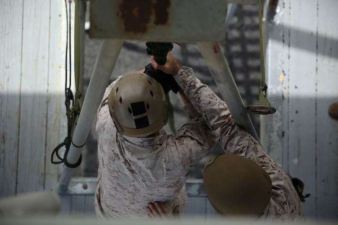A Marine assigned to Company A, 1st Reconnaissance Battalion, 1st Marine Division, prepares to fast-rope out of a rappel tower as part of Helicopter Rope Suspension Techniques training aboard Marine Corps Base Camp Pendleton, Calif., Aug. 17, 2015. Fast-roping is the most commonly used insertion tactic for Reconnaissance Marines during training or real-life missions.