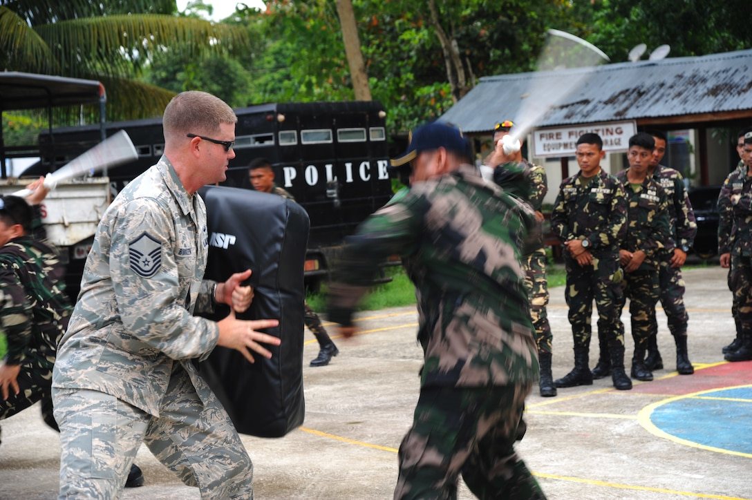 U.S. Air Force Master Sgt. Jeremy Burkeen, from 736th Security Forces Squadron at Andersen Air Force Base, Guam, facilitates non-lethal crowd control training with members of the Philippine national police and Armed Forces of the Philippines during Pacific Angel in Tagbiliran City, Philippines, Aug. 16, 2015. Efforts undertaken during Pacific Angel help multilateral militaries in the Pacific improve and build relationships across a wide spectrum of civic operations, which bolsters each nation's capacity to respond and support future humanitarian assistance and disaster relief operations. (U.S. Air Force photo by Tech. Sgt. Aaron Oelrich/Released)