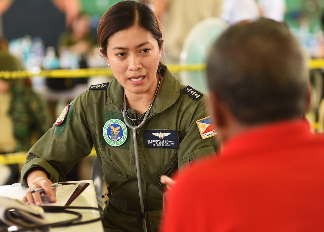 Philippine Air Force Capt. Jacquelyn Corpuz, a PAF flight nurse, questions a patient about his general heath during Pacific Angel's healthcare services outreach, Bohol Province, Philippines, Aug. 16, 2015. The healthcare services outreach program provided general care, optometry services, dental care, physical therapy and a pharmacy. Pacific Angel is a multilateral humanitarian assistance civil military operation, which improves military-to-military partnerships in the Pacific while also providing medical health outreach, civic engineering projects and subject matter exchanges among partner forces.(U.S. Air Force photo by Tech. Sgt. Aaron Oelrich/Released)