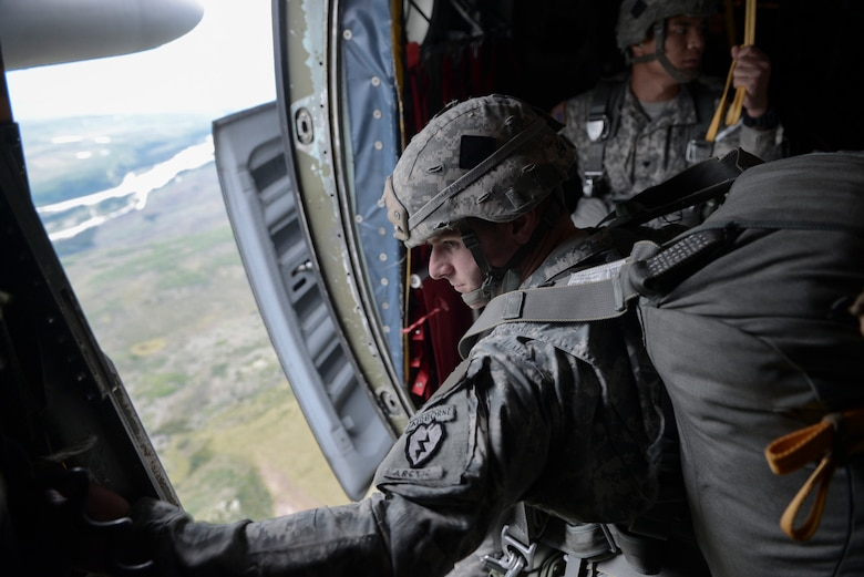 A U.S. Soldier with the 3-509th, 4th Brigade Combat Team (Airborne), 25 Infantry Division, prepares to jump from a C-130 Hercules from Yokota Air Base, Japan, during Red Flag-Alaska at Joint Base Elmendorf-Richardson, Alaska, Aug. 12, 2015. More than 60 U.S. Army Soldiers with the 1-501 Parachute Infantry Regiment and more than 20 Japan Ground Self-Defense Force members jumped from multiple C-130 Hercules during the training. More than 20 allied countries have participated in RED FLAG-Alaska since its conception, improving integration, interoperability and cross-cultural competence. (U.S. Air Force photo by Staff Sgt. Cody H. Ramirez/Released)