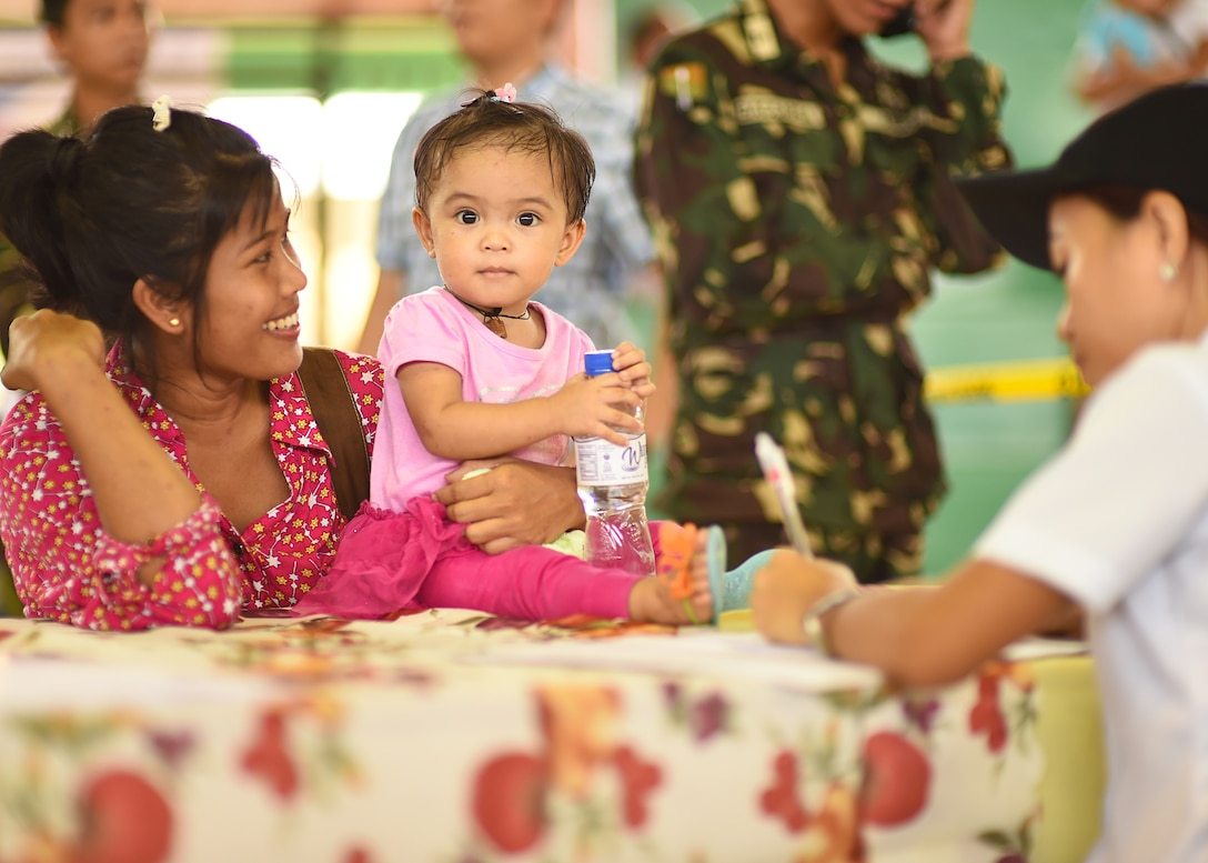 Rayian Carazon and daughter Trica, from Lila, Bohol province, Philippines, process through the register portion of the Health Services Outreach provided as part of the Pacific Angel Philippines mission taking place in Lila, Bohol province, Philippines, Aug. 16, 2015. Pacific Angel is a multilateral humanitarian assistance civil military operation, which improves military-to-military partnerships in the Pacific while also providing medical health outreach, civic engineering projects and subject matter exchanges among partner forces.(U.S. Air Force photo by Tech. Sgt. Aaron Oelrich/Released)