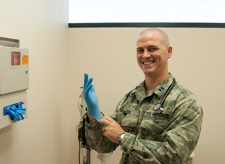 "Capt. Nathan Smith, 90th Medical Operations Squadron Nuclear Operations Clinic element chief, puts on a glove as he poses in an examination room in the 90th Medical Group Medical Treatment Facility on F.E. Warren Air Force Base, Wyo, Aug. 19, 2015. Smith recommends patients seek medical treatment if they exhibit the ""classic triad"" of rhabdomyolyisis symptoms — muscle weakness, muscle pain an dark urine. (U.S. Air Force photo by Senior Airman Jason Wiese)"