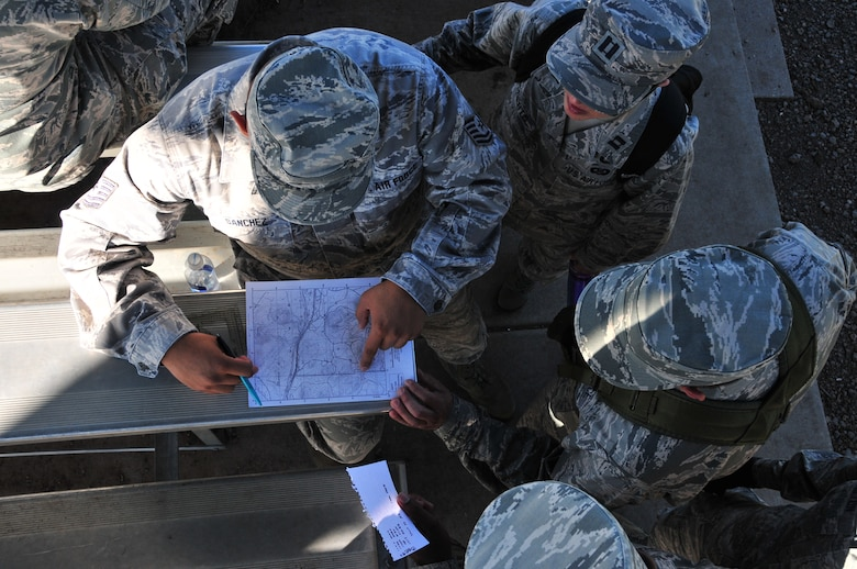 Tech. Sgt. Jimmy Sanchez plots out points on a topographical map during land navigation training with his team, Capt. Tauna Roberts, Airman 1st Class Clyde Samilton and Airman 1st Class Wendell Van Duyne at Camp Navajo, Ariz., Aug. 5. Airmen from the 161st Air Refueling Wing participated in ancillary training which included weapons qualification, self-aid buddy care, ability to survive and operate, land navigation and diversity training.  (U.S. Air National Guard photo by Master Sgt. Kelly Deitloff)