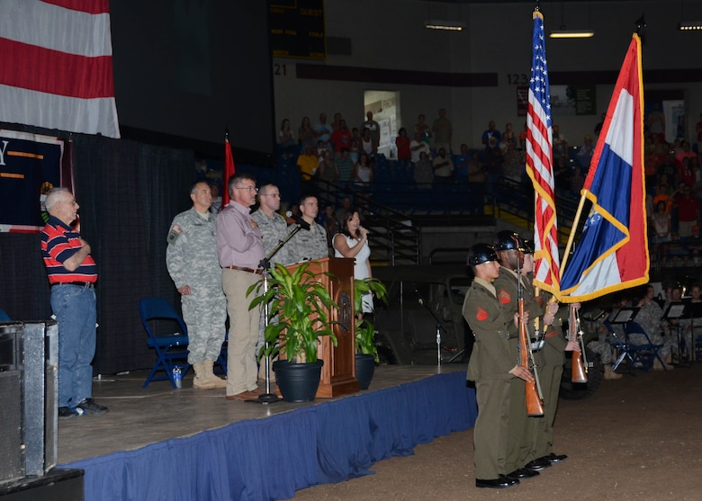 Distinguished guests stand for the singing of the National Anthem by Sarah Alsager, a member in the Missouri Department of Agriculture, and the posting of the colors performed by the Missouri National Guard Funeral Honors Color Guard during the Military Appreciation ceremony at the Missouri State Fair, August 16, 2015. (U.S. Air National Guard photo by Staff Sgt. Brittany Cannon)