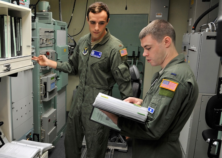2nd Lt. Michael McCrary, 10th Missile Squadron deputy crew commander, left, and 1st Lt. Ian Sylvester, 10th MS crew commander, use a checklist to confirm communications equipment is correctly set Aug. 8, 2015, during a training session in the missile procedures trainer at Malmstrom Air Force Base, Mont., for Global Strike Challenge 2015. The crew is one of three from the 341st Operations Group that will compete Aug. 31 against Minot AFB, N.D., and F.E. Warren AFB, Wyo., in Air Force Global Strike Command's ICBM Operations competition. (U.S. Air Force photo/ John Turner)
