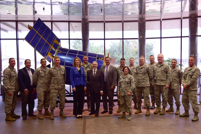 Base leadership poses in front of the Defense Support Program satellite in the Mission Control Station with Lisa Disbrow, Acting Under Secretary of the Air Force, Aug. 18, 2015, on Buckley Air Force Base, Colo. Ms. Disbrow interacted with Airmen in order to gain a better understanding of the mission conducted by the 460th SW.  (U.S. Air Force photo by Airman 1st Class Luke W. Nowakowski/Released)