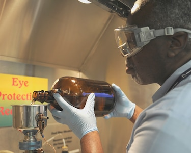 Reggie Moore, 11th Logistics Readiness Squadron fuels technician, performs a bottle-method test Aug. 19, 2015, on Joint Base Andrews, Md. This test checks the solid content in the fuel to ensure the delivery is free of particulate matter. (U.S. Air Force photo by Senior Airman Preston Webb/RELEASED)