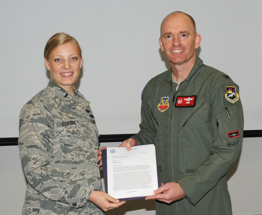 Oregon Air National Guard Col. Paul T. Fitzgerald, 142nd Fighter Wing commander, right, presents the Air Combat Command Overall Superior Performer award to 1st Lt. Amber Osborne, assigned to the 142nd Fighter Wing Operations Group, left, during a briefing that concluded the Unit Effectiveness Inspection, Aug. 18, 2015, Portland Air National Guard Base, Ore. (U.S. Air National Guard photo by Master Sgt. Shelly Davison, 142nd Fighter Wing Public Affairs)
