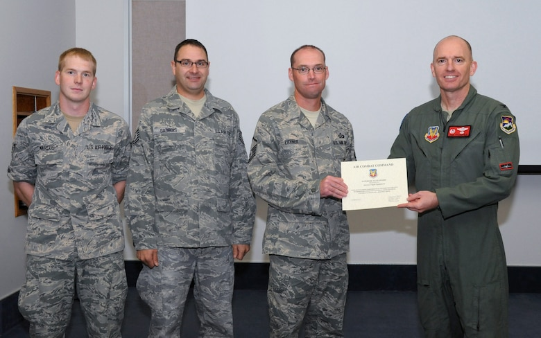 Oregon Air National Guard Col. Paul T. Fitzgerald, 142nd Fighter Wing commander, right, presents the Air Combat Command Superior Team Award to the Aircrew Flight Equipment team in attendance for a briefing following the Unit Effectiveness Inspection, Aug. 18, 2015, Portland Air National Guard Base, Ore. The three members representing the entire team assigned to the 142nd Fighter Wing Operations Group are (left-right) Airman 1st Class Cory Marcus, Tech. Sgt. Gregory Gadbois and Master Sgt. Mike Larner. (U.S. Air National Guard photo by Master Sgt. Shelly Davison, 142nd Fighter Wing Public Affairs)