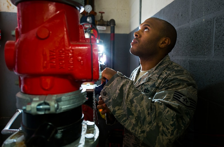 Staff Sgt. Lewis Thomas, 11th Civil Engineer Squadron water and fuels systems specialist, checks a pressure gauge at Hangar 13 on Joint Base Andrews, Md., Aug. 19, 2015. Thomas and his crew were repairing the facilities fire suppression system, which is crucial for hangars that store aircraft. (U.S. Air Force photo by Staff Sgt. Chad C. Strohmeyer)(Released)