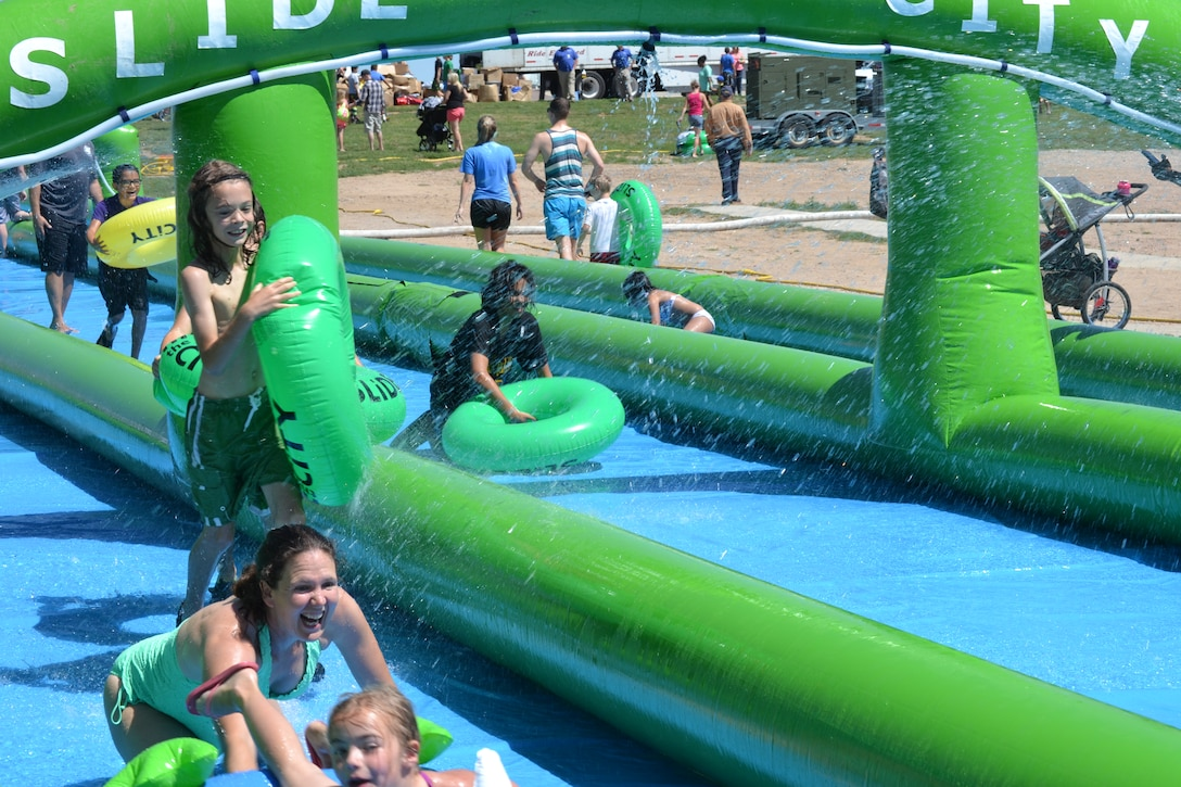 Sliders laugh and smile while they come down the giant slip-and-slide during Operation Slide Schriever Friday, Aug. 14, 2015, at Schriever Air Force Base, Colorado. The event, a collaboration between Schriever and the organizers of Slide the City, brought a sample slide from that event, which took place in Colorado Springs Saturday, Aug. 15, 2015, to Schriever. (U.S. Air Force photo/Brian Hagberg)