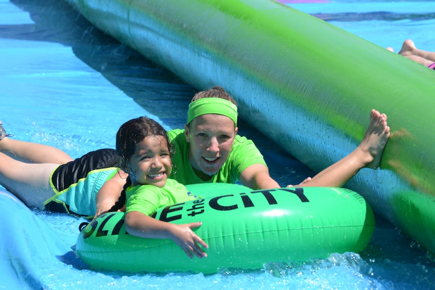 Kristin Moseley, Schriever School Age Program assistant, helps push Adrienne Sanchez, SAP student, down the giant slip-and-slide during Operation Slide Schriever Friday, Aug. 14, 2015, at Schriever Air Force Base, Colorado. Hundreds of people turned out for the free event which also included food, drinks and a kid's zone. (U.S. Air Force photo/Brian Hagberg)