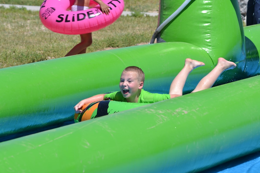 Tyler Lukenbaugh, a Schriever School Age Program student, screams while sliding down a giant slip-and-slide Friday, Aug. 14, 2015, during Operation Slide Schriever at Schriever Air Force Base, Colorado. Hundreds of people turned out for the free event which also included food, drinks and a kid's zone. (U.S. Air Force photo/Brian Hagberg)