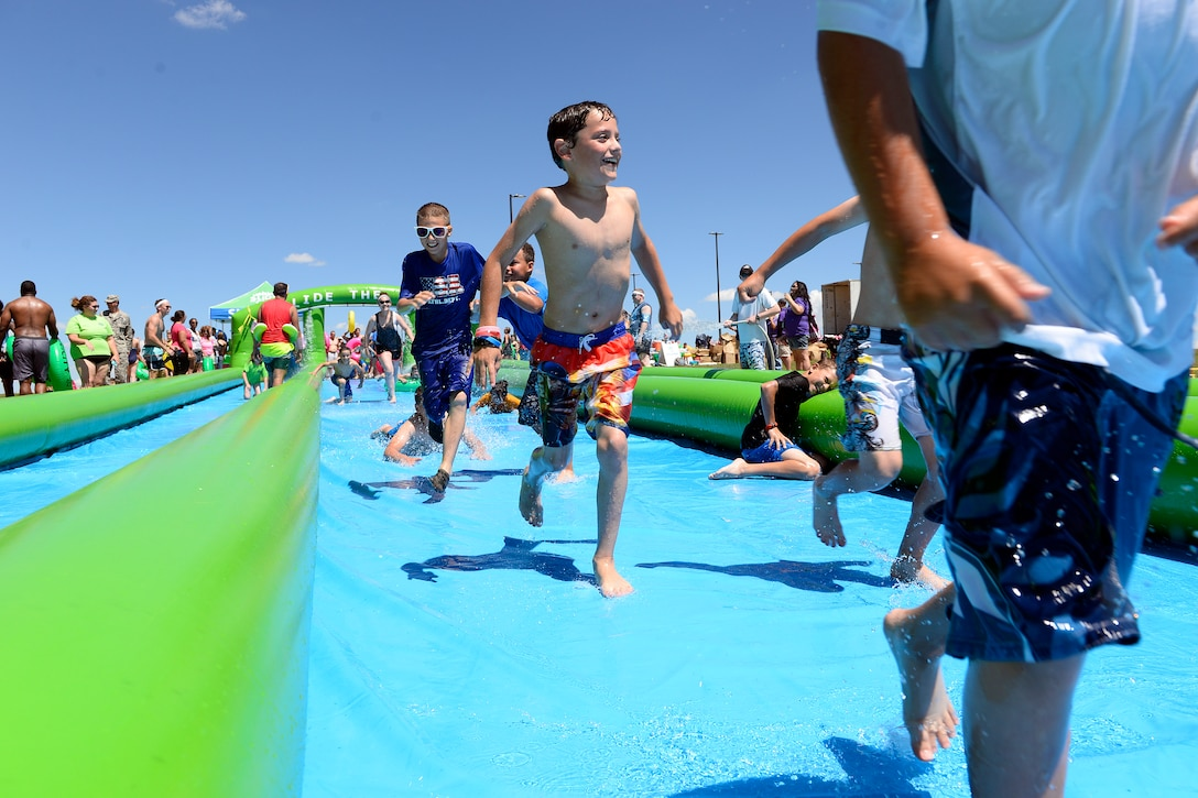 Youth run down a giant slip-and-slide during Operation Slide Schriever Friday, Aug. 14, 2015 at Schriever Air Force Base, Colorado. The event, a collaboration between Schriever and the organizers of Slide the City, brought a sample slide from that event, which took place in Colorado Springs Saturday, Aug. 15, 2015, to Schriever.  (U.S. Air Force photo/Christopher DeWitt)