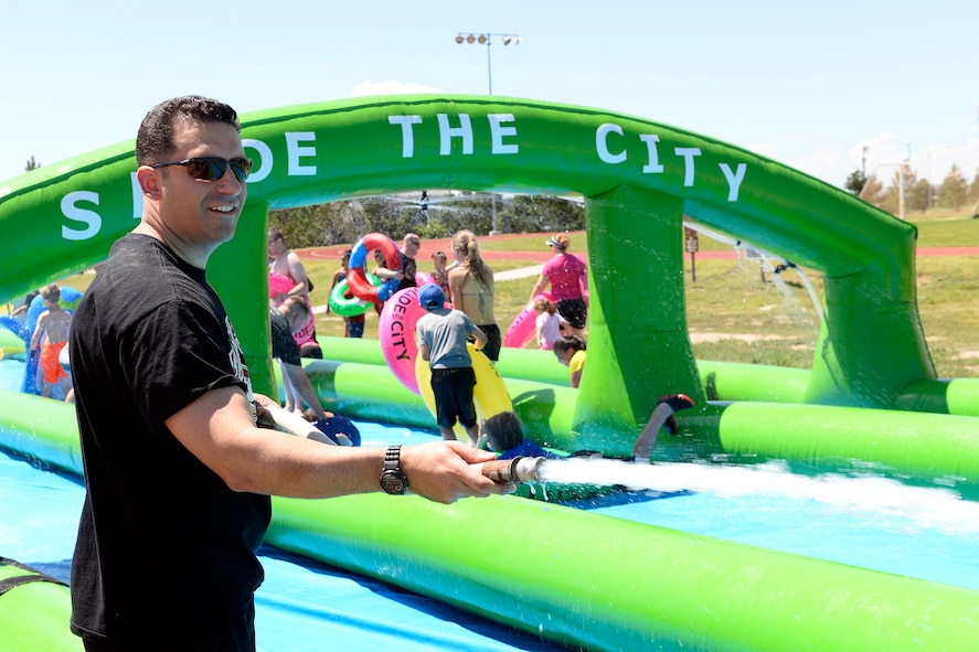Col. Jason Janaros, 50th Mission Support Group commander, sprays water on participants sliding down the giant slip-and-slide during Operation Slide Schriever Friday, Aug. 14, 2015 at Schriever Air Force Base, Colorado. Hundreds of people turned out for the free event, including youth from the Schriever School Age Program and Ellicott School District. (U.S. Air Force photo/Christopher DeWitt)
