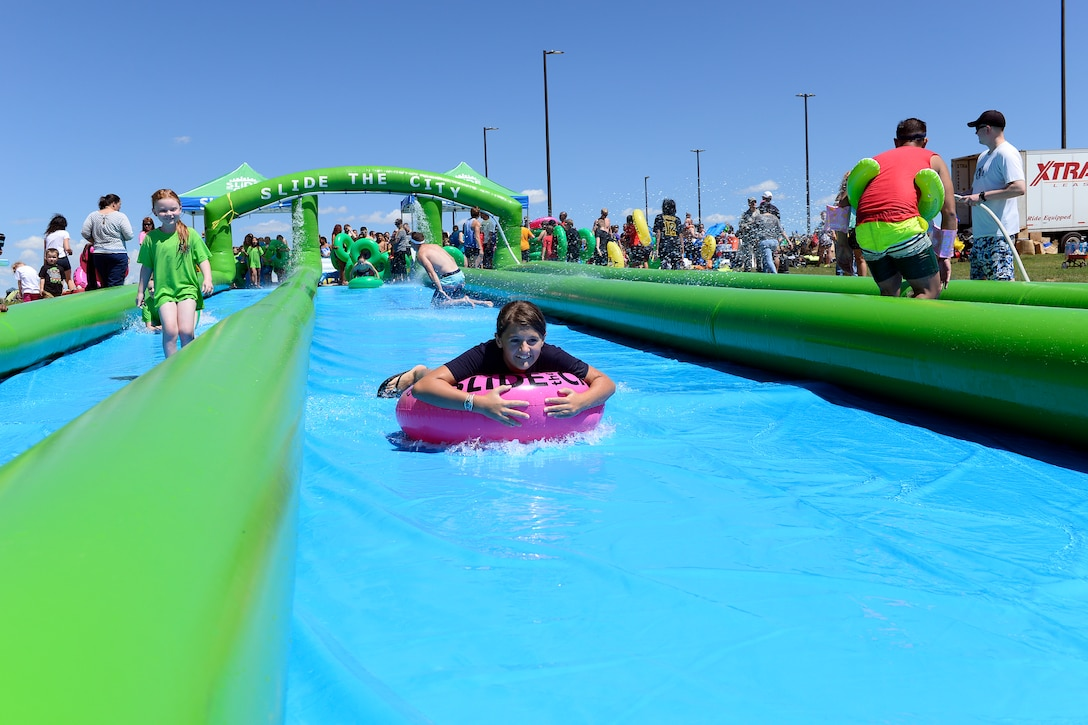 Youth from the Schriever School Age Program and Ellicott School District slide down a giant slip-and-slide Friday, Aug. 14, 2015, during Operation Slide Schriever at Schriever Air Force Base, Colorado. The event, a collaboration between Schriever and the organizers of Slide the City, brought a sample slide from that event, which took place in Colorado Springs Saturday, Aug. 15, 2015, to Schriever.  (U.S. Air Force photo/Christopher DeWitt)