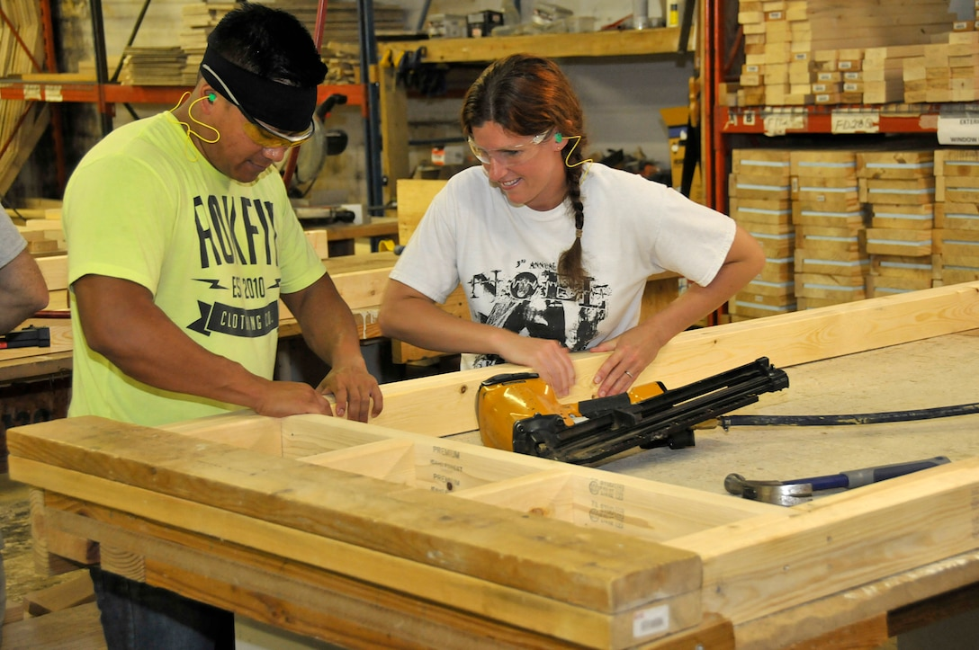 KNOXVILLE, Tenn. - Tech. Sgt. Kalon Pang and Master Sgt. Cindy Dickson, instructors assigned to the I.G. Brown Training and Education Center on McGhee Tyson Air National Guard Base, assemble a doorframe August 18, 2015, that will be used in a home building project. About a dozen military volunteers took part in the two-day Habitat for Humanity project here inside the organization's wood shop. (U.S. Air National Guard photo by Master Mike R. Smith/Released)