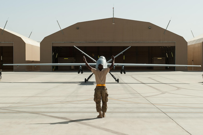 A U.S. Airman assigned to the 62nd Expeditionary Reconnaissance Squadron directs a MQ-9 Reaper aircraft at Kandahar Airfield, Afghanistan, Aug. 14, 2015.  The 62nd ERS operates the MQ-1B Predator and Reaper aircraft and provides world-class close air support, intelligence, surveillance and reconnaissance capabilities in Afghanistan. (U.S. Air Force photo by Tech. Sgt. Joseph Swafford/Released)