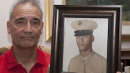 """Benjamin """"Ben"""" Palermo holds a photo of himself when he was serving on active duty in the Marine Corps in his home in San Antonio, Texas, June 4, 2015. Palermo served with G Company, 2nd Battalion, 4th Marine Regiment during Operation Starlite during August 1965 in Vietnam."""