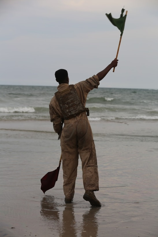 Lance Cpl. Rameses Spellman, a Crewman with 1st Platoon, Bravo Company,2nd  Assault Amphibian  Battalion waves a flag to signal the go ahead for the next amphibious assault vehicle to start their push into the surf on Onslow Beach aboard Camp Lejeune, N.C. Aug. 17, 2015. During this training exercise the battalion conducted gator squares and beach assaults. (U.S. Marine Corps photo by Pfc. Miranda Faughn/Released)