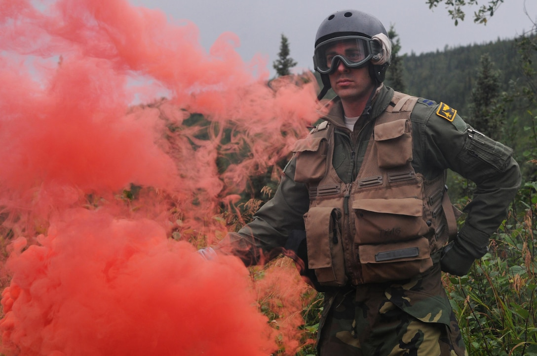 U.S. Air Force Capt. Austin Cox, a pilot with the Minnesota Air National Guard's 148th Fighter Wing, holds a smoke flare to identify his location during an isolated personnel recovery exercise Aug. 13, 2015, at Eielson Air Force Base, Alaska, while participating in RED FLAG-Alaska (RF-A) 15-3.  RF-A is a Pacific Air Forces commander-directed field training exercise for U.S. and partner nation forces, providing combined offensive counter-air, interdiction, close air support and large force employment training in a simulated combat environment.  (U.S. Air Force photo by Master Sgt. Ralph Kapustka/Released)