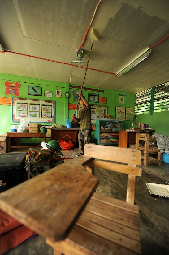 A member of the Armed Forces of the Philippines paints a class room at Dao Elementary school in Bohol Province, Philippines, Aug. 18, 2015. Repairs to the school were part Pacific Angel Philippines' engineering civic action projects that included members from the U.S. Air Force, U.S. Army and U.S. Marine Corps along with service members from the Philippines and Australia. This was one of six schools that underwent construction, reaping everything from walkways, lighting, electrical wiring, to roof replacement, and paint. Pacific Angel is a multilateral humanitarian assistance civil military operation, which improves military-to-military partnerships in the Pacific while also providing medical health outreach, civic engineering projects and subject matter exchanges among partner forces. (U.S. Air Force photo by Tech. Sgt. Aaron Oelrich/Released)