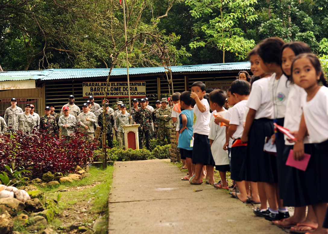 Students from Bartolome Doria Elementary School stand ready to present a token of gratitude after members from the U.S. Air Force, U.S. Army and U.S. Marine Corps along with service members from the Philippines and Australia came together to repair their school as a part of Pacific Angel Philippines in Bohol Provence, Philippines, Aug. 16, 2015. Efforts undertaken during Pacific Angel help multilateral militaries in the Pacific improve and build relationships across a wide spectrum of civic operations, which bolsters each nation's capacity to respond and support future humanitarian assistance and disaster relief operations. (U.S. Air Force photo by Tech. Sgt. Aaron Oelrich/Released)