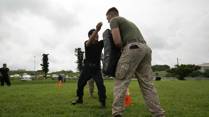 A Japanese security guard executes a knee strike during nonlethal weapons and level one oleoresin capsicum spray training aboard Camp Foster, Okinawa, Japan, Aug. 14. According to Delekto, the security augmentation force instructor and staff noncommissioned officer with mobile training team, Provost Marshal's Office, Marine Corps Base Camp Smedley D. Butler, Marine Corps Installations Pacific, nonlethal weapons training includes all weapons and techniques that are not inherently deadly, such as batons, defensive tactics, pepper-based spray, and mechanical-advantage control holds.