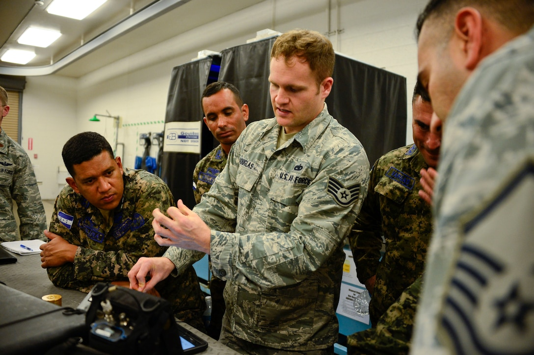 U.S. Air Force Staff Sgt. Ian Douglas, 355th Equipment Maintenance Squadron nondestructive inspections lab journeyman, teaches members of the Honduran Air Force how to conduct ultrasonic testing during a subject matter expert exchange event on Davis-Monthan AFB, Ariz., Aug. 19, 2015. Ultrasonic Testing uses ultrasonic vibrations to detect internal defects, delaminations, disbonds, and discontinuities. The five members from the Honduran Air Force teamed up with 12th Air Force (Air Forces Southern) and the 355th EMS for a subject matter expert exchange that focused on a variety of nondestructive inspections lab processes and maintenance safety standards. (U.S. Air Force photo by Tech. Sgt. Heather Redman/Released)