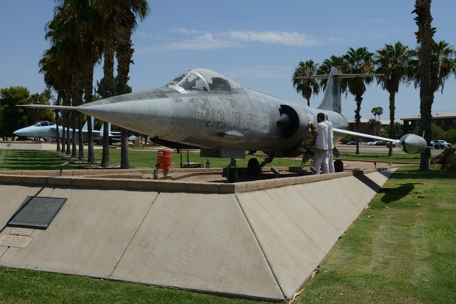 James Bridges and Hayden Yager, civilian contractors, prepare the F-104C Starfighter static display for painting at Luke Air Force Base, Arizona, Aug. 12, 2015. All the static displays in the airpark will be repainted and have maintenance performed by the end of the year. (U.S. Air Force photo by Senior Airman James Hensley)