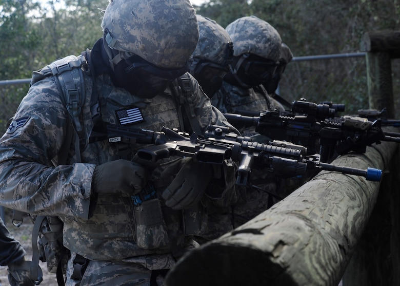 A team of 325th Security Forces Squadron members perform a final operational check of their training rifles before an exercise Aug. 18 in preparation of a Shoot, Move and Communicate exercise with emphasize on self-aid and buddy care under fire. The purpose of the exercise was to maintain certifications and give Airmen experience in SABC in a simulated combat area. (U.S. Air Force photo by Airman 1st Class Solomon Cook/Released)