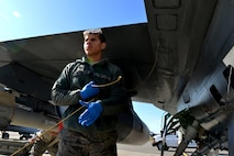 A U.S. Air Force crew chief performs regular checks on a U.S. Air Force F-16 Fighting Falcon assigned to the Minnesota Air National Guard's 148th Fighter Wing out of Duluth, Minn., on the Eielson Air Force Base, Alaska, flightline Aug. 14, 2015, as 354th Logistics Readiness Squadron Airmen refuel the aircraft in preparation for its next RED FLAG-Alaska (RF-A) 15-3 sortie. RF-A is a Pacific Air Forces commander-directed field training exercise for U.S. and partner nation forces, providing combined offensive, counter-air, interdiction, close-air support, and large-force employment training in a simulated combat environment. (U.S. Air Force photo by Airman 1st Class Kyle Johnson)