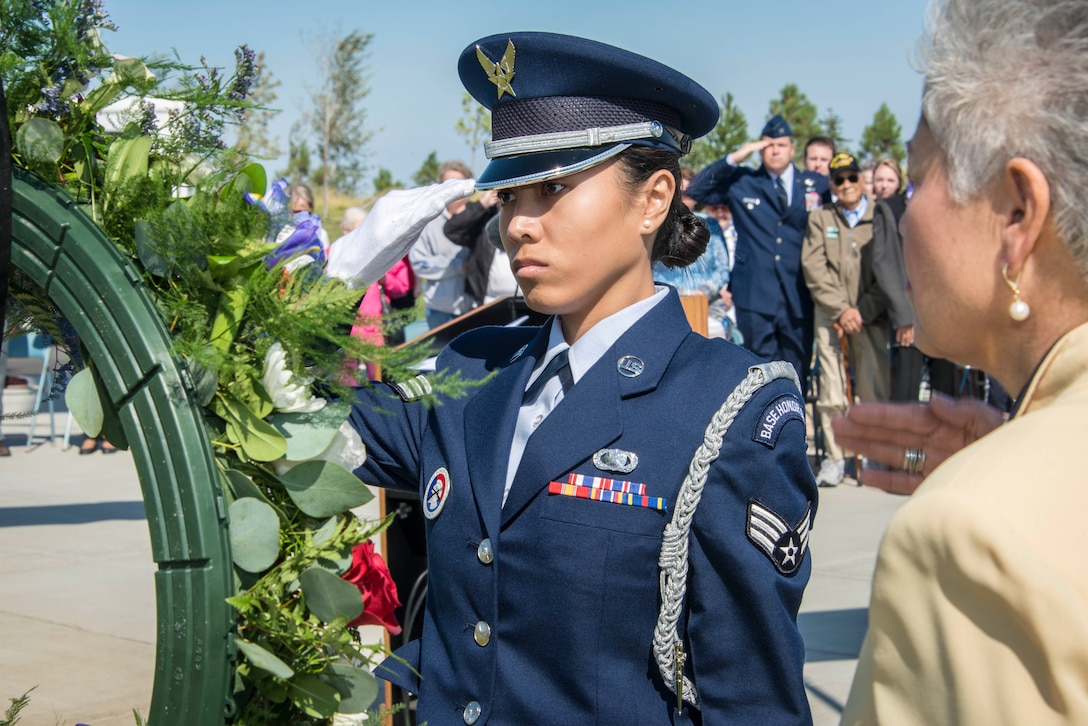 Senior Airman Janelle Patiño, Fairchild Honor Guard member, and Alfie Alvarado, Washington State Department of Veterans Affairs director, salute the ceremonial wreath during the commemoration ceremony for the 70th anniversary to the end of World War II Aug. 15, 2015, at the Washington State Veterans Cemetery in Medical Lake, Wash. Col. Matthew Fritz, 92nd Air Refueling Wing vice commander, can be seen in the background also saluting and flanked by WWII veterans and their families. The gift of flowers at a memorial site is a ritual that occurs around the world and understood in nearly every culture. The floral tributes at funeral bespeak both the beauty and the brevity of life and evoke memories of other days. (U.S. Air Force photo/Staff Sgt. Benjamin W. Stratton)