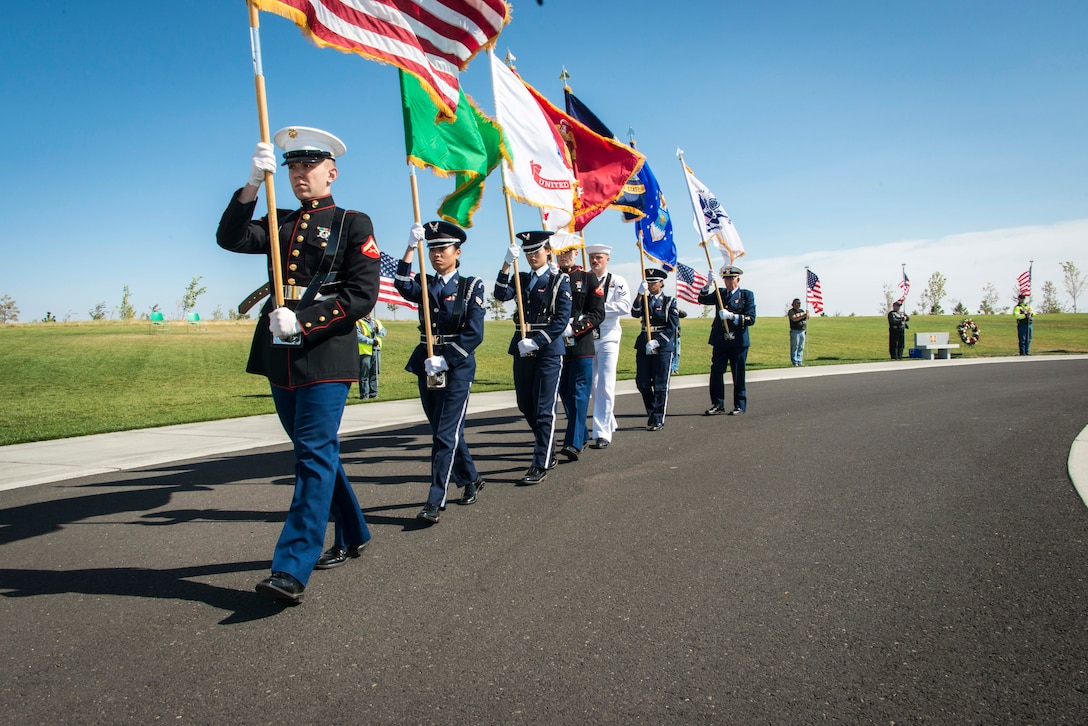 Multi-service color guard marches away following the kickoff of the commemoration ceremony for the 70th anniversary to the end of World War II Aug. 15, 2015, at the Washington State Veterans Cemetery in Medical Lake, Wash. Color guards present the national flag and other flags appropriate to its position in the chain of command. In addition to the flag bearers, who are positioned in the center of the color guard, there are two or more individuals who carry rifles and or sabers in a typical formation. (U.S. Air Force photo/Staff Sgt. Benjamin W. Stratton)