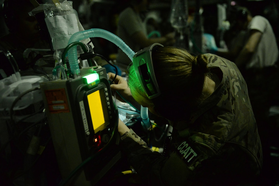 U.S. Air Force Capt. Deann Hoelscher, 455th Expeditionary Aeromedical Evacuation Squadron Critical Care Air Transport Team physician deployed from the 60th Medical Group at Travis Air Force Base, California, checks on a patient's status during an aeromedical evacuation mission aboard a C-17 Globemaster III aircraft from Bagram Airfield, Afghanistan, to Ramstein Air Base, Germany, Aug. 9, 2015. The 455th EAES' CCATT is a three-person, highly specialized medical team consisting of a physician who specializes in an area of critical care or emergency medicine, a critical care nurse and a respiratory therapist. The CCATT is charged with providing critical care to the sick and wounded as they are moved thousands of miles onboard U.S. cargo aircraft to receive full-time care elsewhere.  (U.S. Air Force photo by Maj. Tony Wickman)