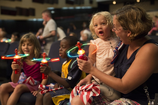 Katy Corrigan, two years, and her mother Mary Corrigan, enjoy the Sesame Street performance by the United Services Organization Experience for Military Families at the Sakura Theater aboard Marine Corps Air Station Iwakuni, Japan, Aug. 14, 2015. Families in attendance received a special Sesame Street toy and reading material outlining the importance of military families adjusting to change.