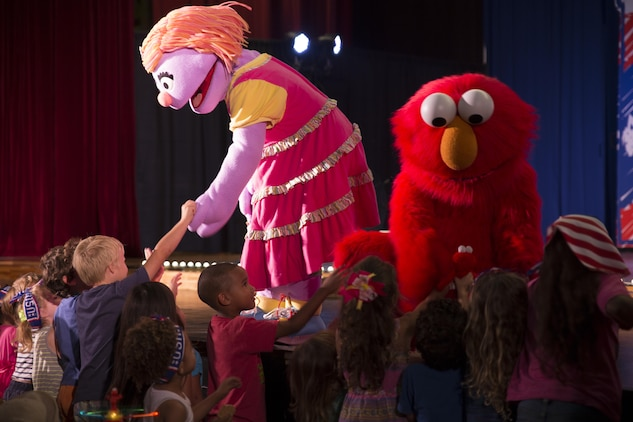 "Katie and Elmo greet children at the Sesame Street performance delivered by the United Services Organization Experience for Military Families at the Sakura Theater aboard Marine Corps Air Station Iwakuni, Japan, Aug. 14, 2015. The program, ""Katie is Moving to a New Base,"" is designed to help children of military families transition during a permanent change of station. Military kids may relate to Katie's situation and could learn how to deal with a difficult move away from family and friends."