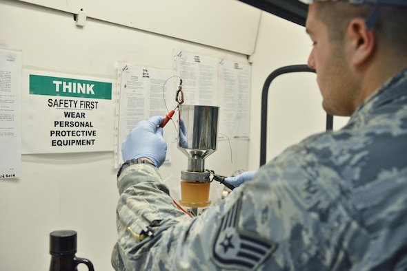 Staff Sgt. David Ramirez, 379th Expeditionary Logistic Readiness fuels laboratory, places grounded cables