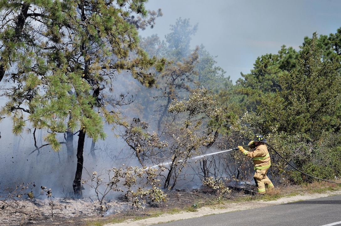 Firefighters from the 106th Rescue Wing assist with extinguishing a brush fire in Westhampton, N.Y., on Aug. 10, 2015. Altogether, eight brush trucks, seven tankers and 14 different fire departments worked together to battle the blaze which destroyed four acres of land along the west side of Old Riverhead Road. (New York Air National Guard/Staff Sgt. Christopher S Muncy)