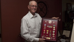 """Homer """"Mike"""" Jenkins, a Marine Vietnam veteran, holds a shadow box highlighting his service in the Marines at his home near Hughes Springs, Texas, June 5, 2015. Jenkins did two tours in Vietnam, the first as an advisor to Vietnamese troops; his second tour, he was a company commander leading Marines in combat."""